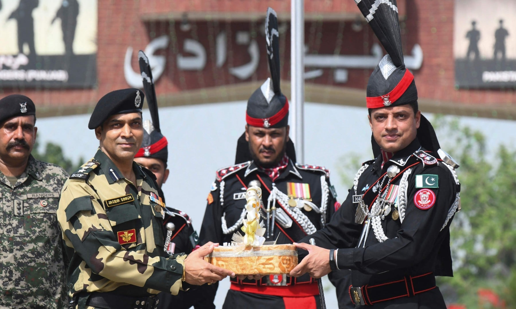 Pakistani Ranger Wing Commander Hassan (R) presents sweets to Indian Border Security Force (BSF) Commandant Jasbir Singh (2L) during a ceremony to celebrate Pakistan's 75th Independence Day at the India-Pakistan Wagah border post on August 14. — AFP