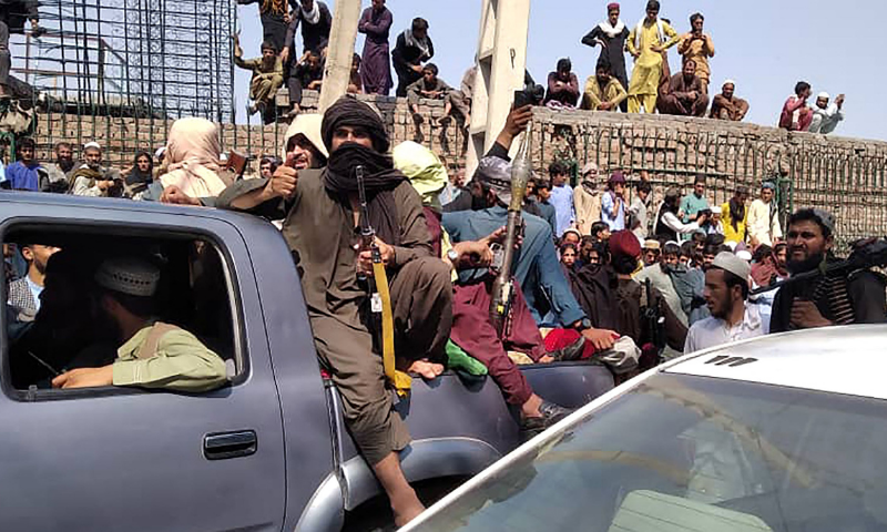 Taliban fighters sit on a vehicle along the street in Jalalabad on Sunday. — AP