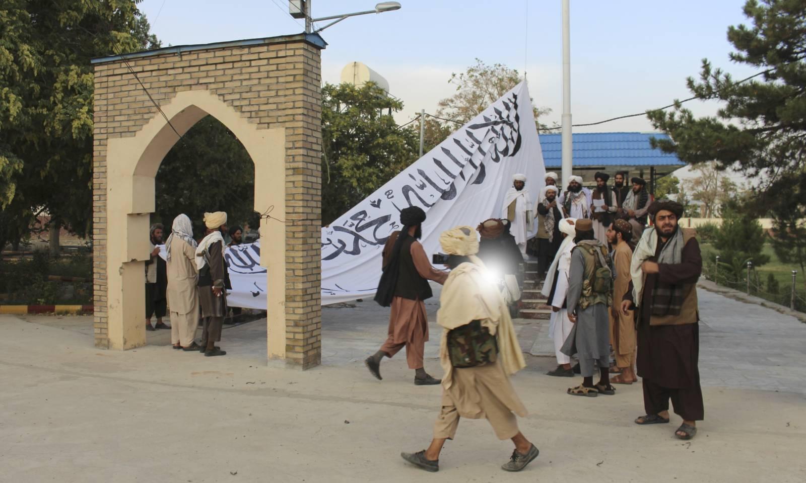 طالبان جنوبی صوبے کے گورنر ہاؤس پر اپنا جھنڈا لہرا  رہے ہیں—فوٹو: اے پی
