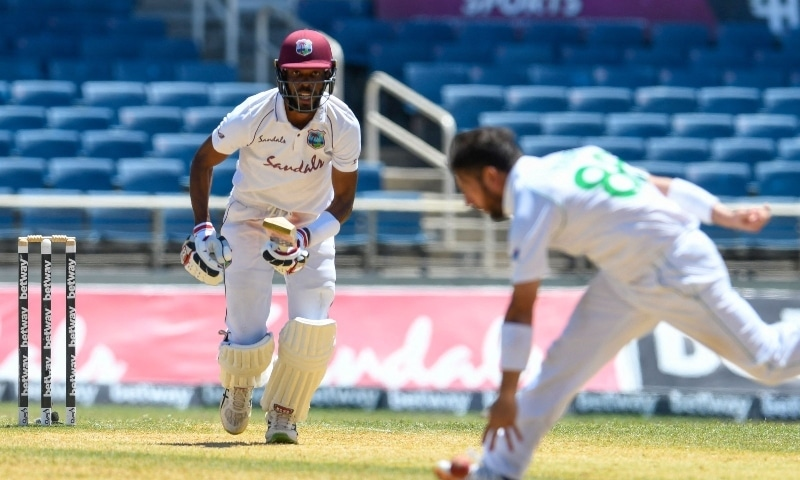 Roston Chase (L) of West Indies hits past Yasir Shah (R) of Pakistan during day 4 of the 1st Test between West Indies and Pakistan at Sabina Park on August 15. — AFP