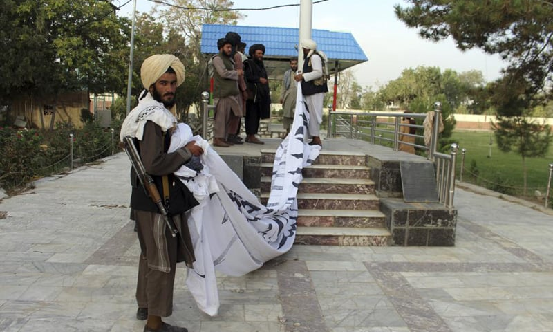 Taliban fighters raise their flag at the Ghazni provincial governor's house, in Ghazni, Afghanistan. — Reuters
