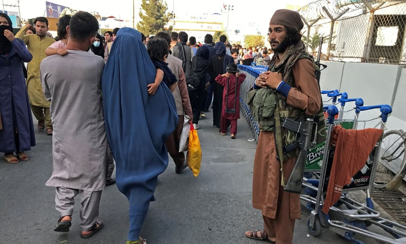 A member of Taliban stands guard as people walk at the entrance gate of Hamid Karzai International Airport in Kabul, Afghanistan. — Reuters