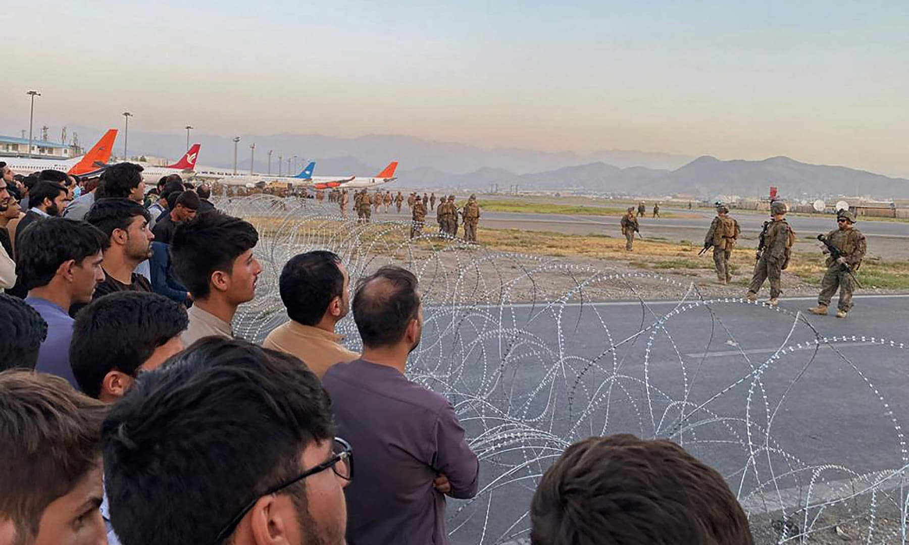 Afghans (L) crowd at the airport as US soldiers stand guard in Kabul, Afghanistan on August 16, 2021. — AFP