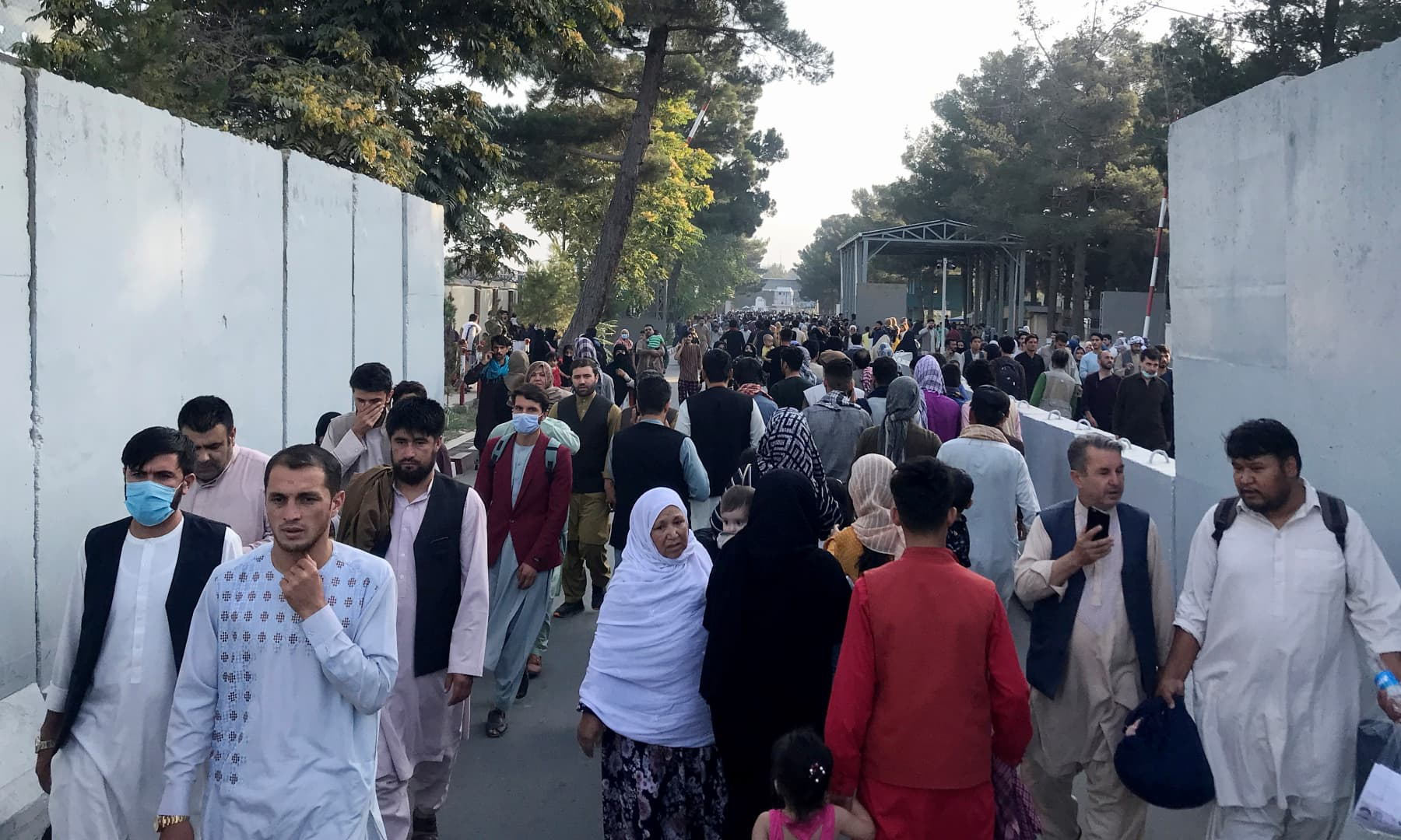 People walk at the entrance gate of Hamid Karzai International Airport in Kabul, Afghanistan on August 16, 2021. — Reuters