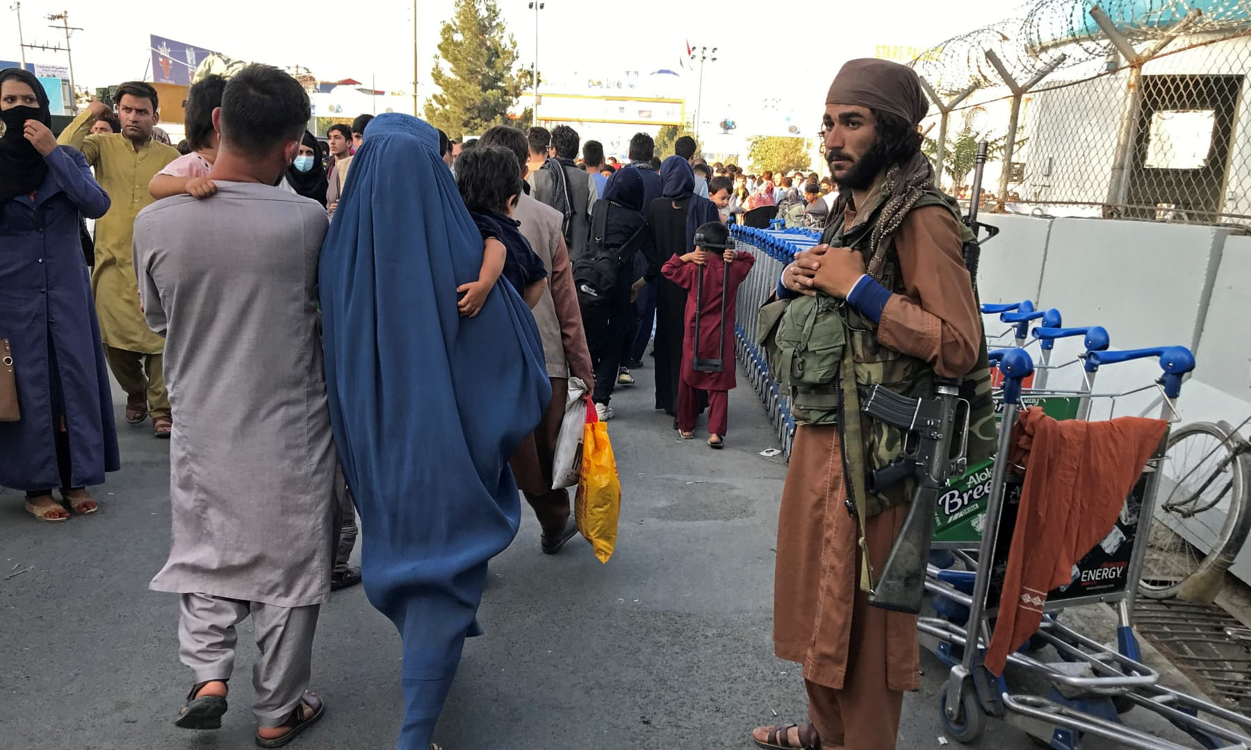A member of the Taliban stands guard as people walk at the entrance gate of Hamid Karzai International Airport in Kabul, Afghanistan on August 16, 2021. — Reuters