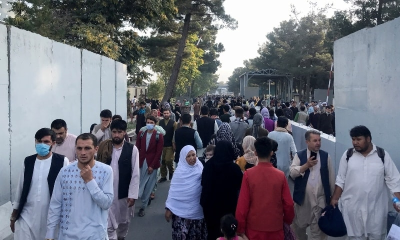 People walk at the entrance gate of Hamid Karzai International Airport in Kabul on August 16. — Reuters
