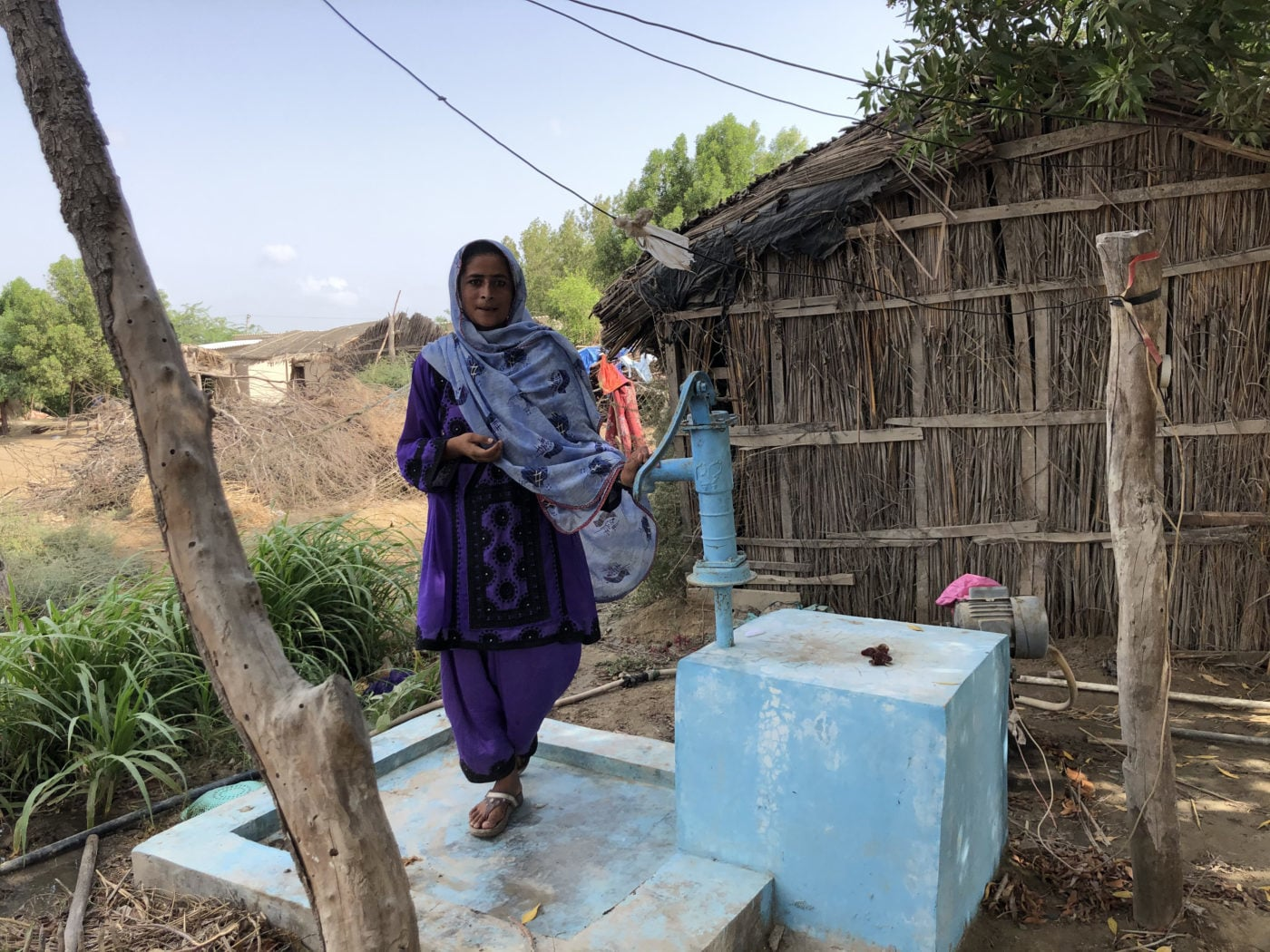 Malda Barkat stands next to a hand pump near her house in the village of Rato Khan Rind, in Thatta district. The intermittent supply means villagers must fetch water from a distance on a donkey cart. — Photo by Zofeen Ebrahim