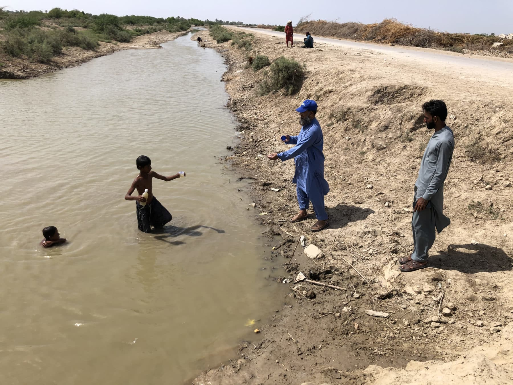 A young volunteer gets a water sample from the canal near the village of Ahmed Raju in Badin district. — Photo by Zofeen Ebrahim