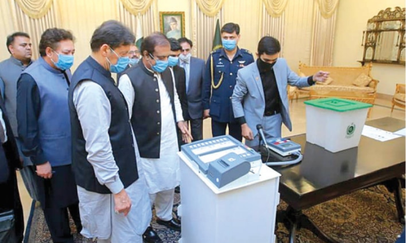Prime Minister Imran Khan and ministers Shibli Faraz and Fawad Chaudhry view a demonstration of a locally made electronic voting machine on Aug 5. — White Star/File