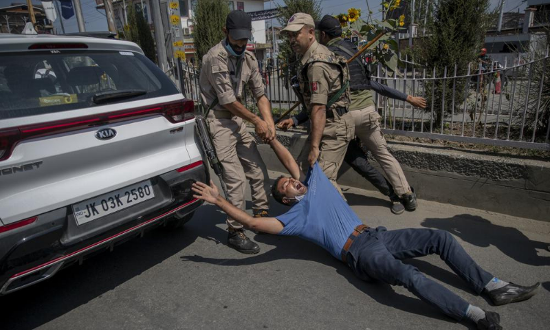 Indian policemen detain a Kashmiri Shia for participating in a procession in central Srinagar area of Indian occupied Kashmir on Tuesday. — AP