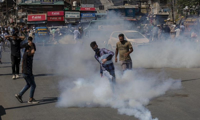 A Kashmiri Shia mourner kicks an exploded tear gas canister during a procession in central Srinagar area of Indian occupied Kashmir on Tuesday. — AP