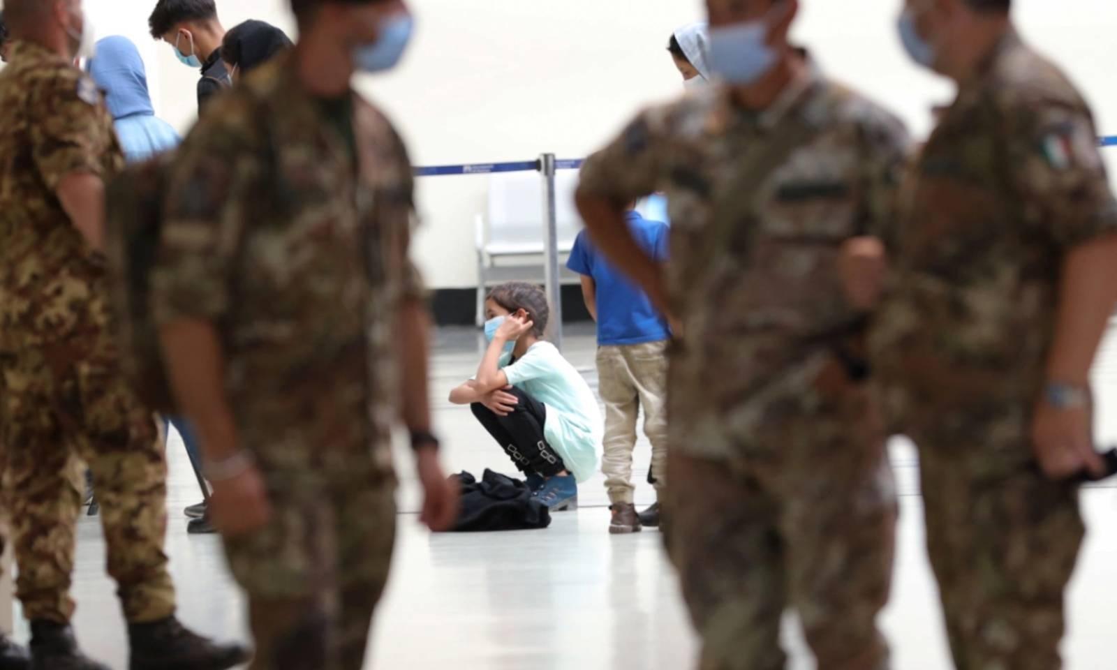 افغان لڑکی اٹلی کے ایئرپورٹ پر قطار میں بیٹھی اپنی باری کا انتظار کررہی ہے —فوٹو:رائٹرز