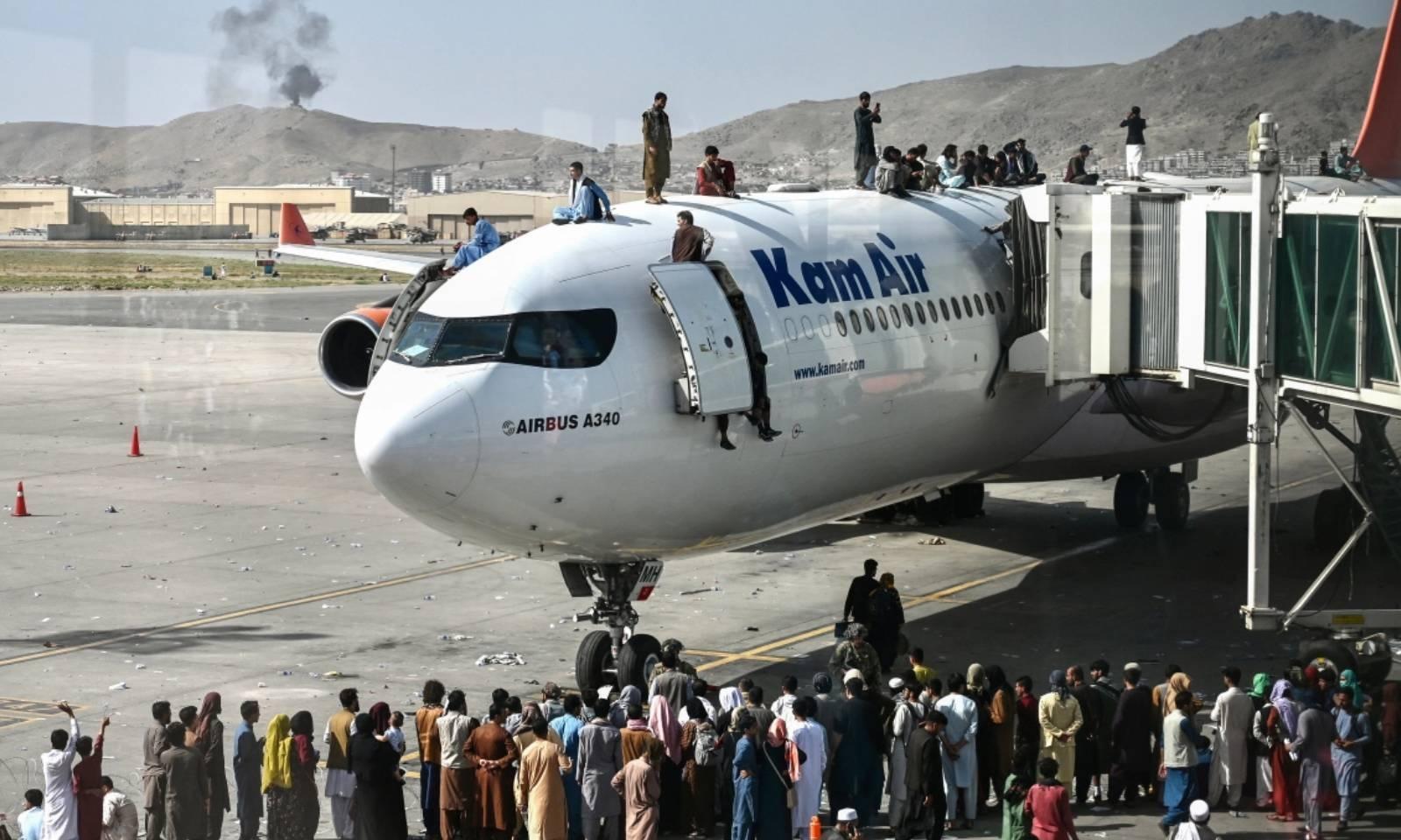 کابل ایئرپورٹ پر افغان شہری طیارے کے اوپر اور اردگرد موجود ہیں — فوٹو: اے ایف پی