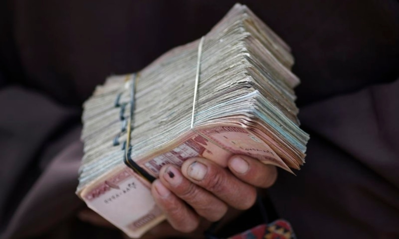 A money changer holds a stack of Afghan currency on a street in central Kabul on April 2, 2014. — Reuters