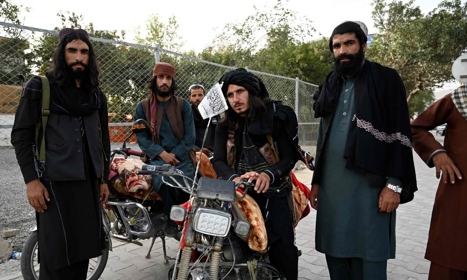 Taliban fighters stand along a road in Kabul on August 18 after the Taliban's military takeover of Afghanistan. — AFP