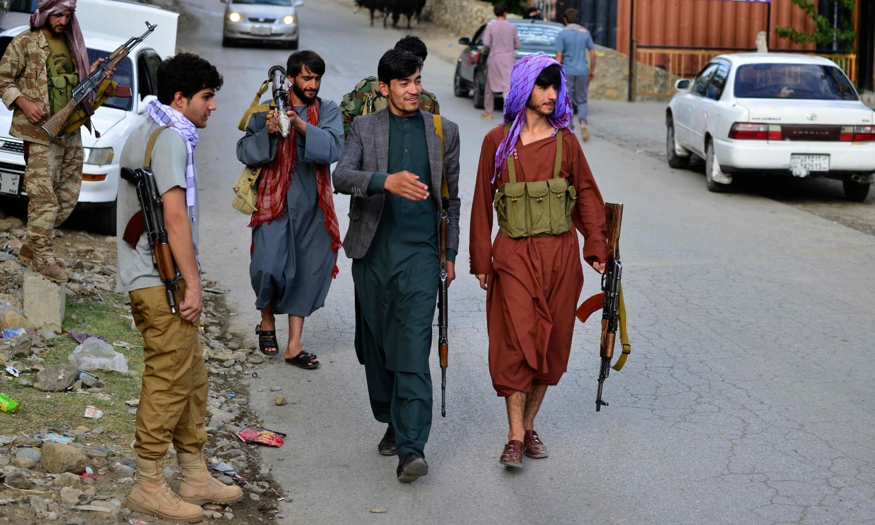 Armed men, supporting the Afghan security forces against the Taliban, walk along a road in Bazarak, Panjshir province, on August 18. — AFP