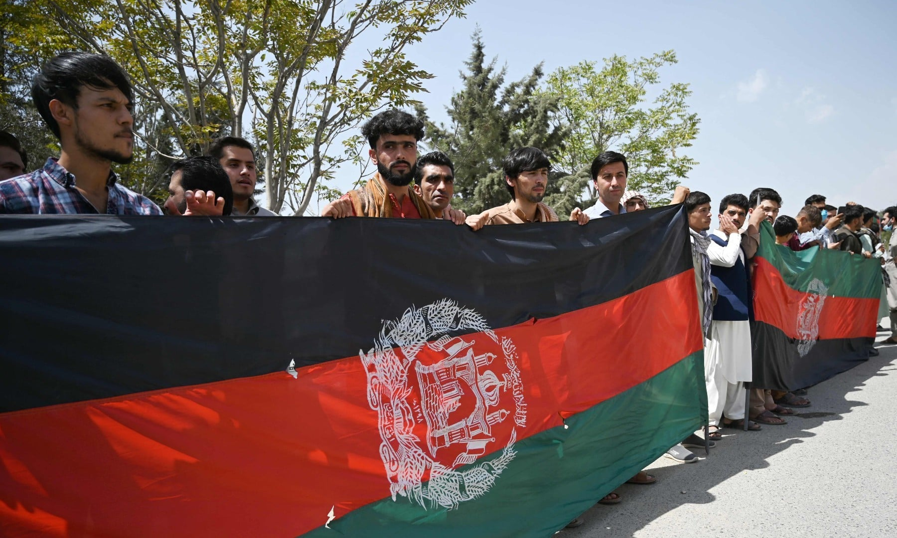 Afghans celebrate the 102nd Independence Day of Afghanistan with the national flag in Kabul on August 19. — AFP