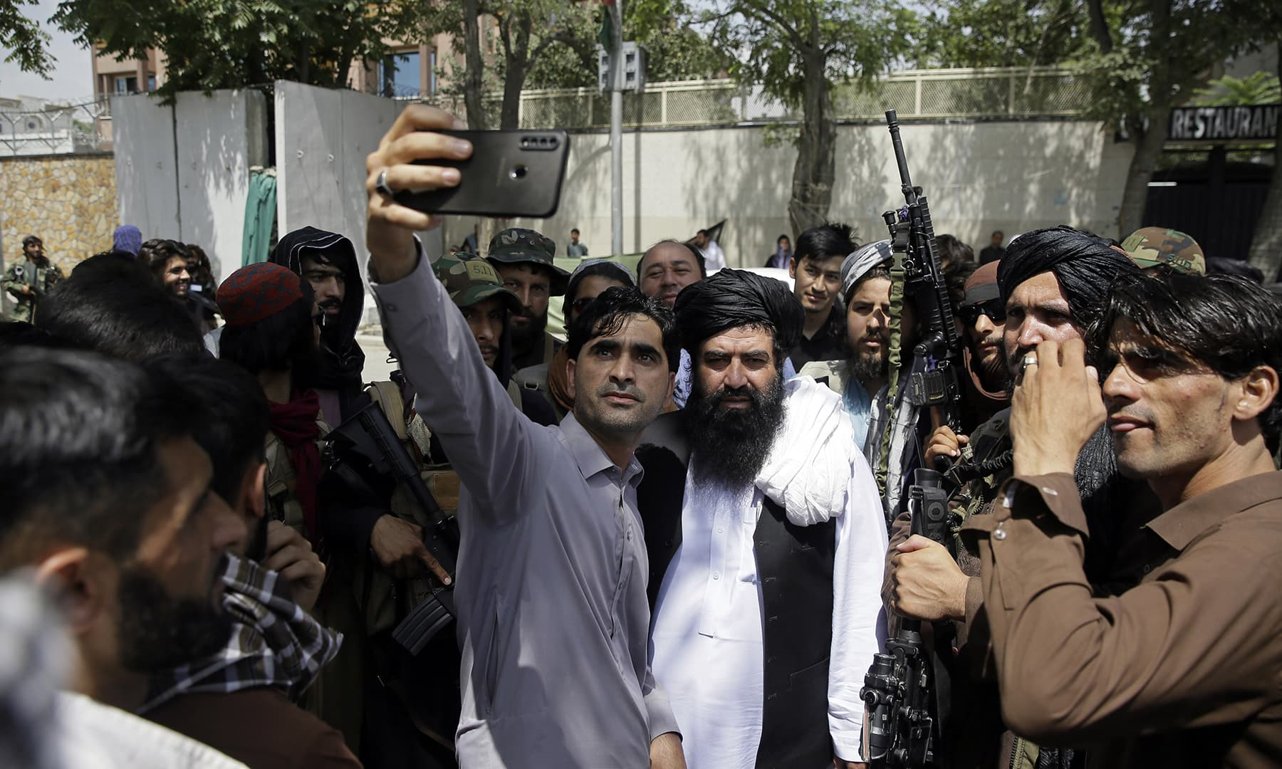 An Afghan takes a selfie with Taliban fighters on patrol in Kabul, Thursday, Aug 19. — AP