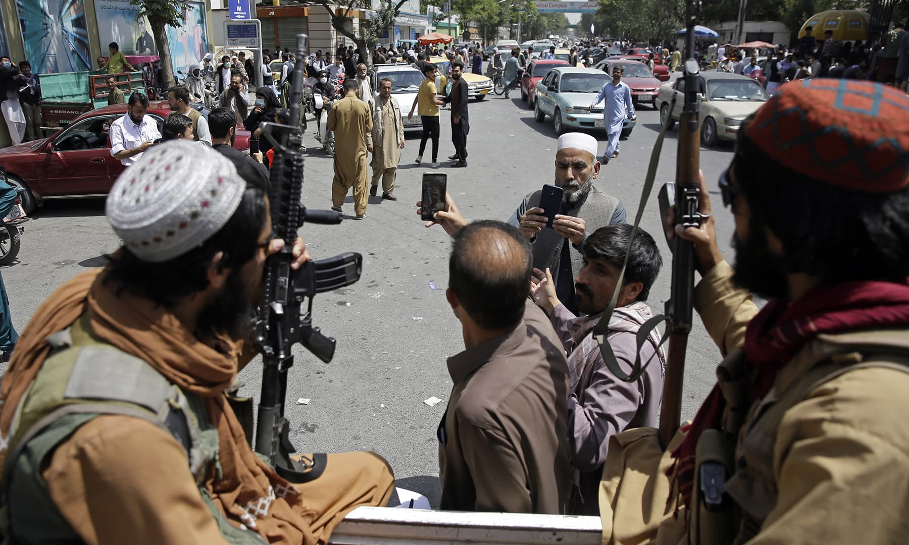 Afghans take a selfie with Taliban fighters during patrol in Kabul, Thursday, Aug 19. — AP