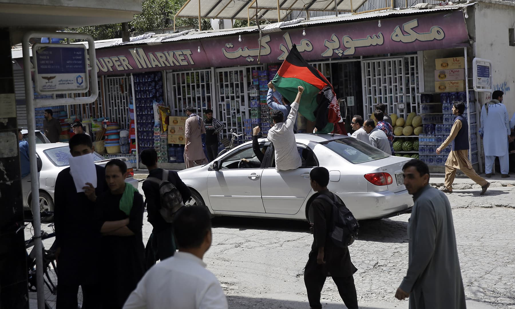 Afghans wave a national flag on their Independence Day, in Kabul, Thursday, Aug 19. — AP