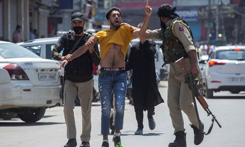 In this file photo, taken on August 17, 2021, Indian policemen detain a Kashmiri Muslim as devotees defy restrictions for a Muharram procession in Srinagar. — AFP/File
