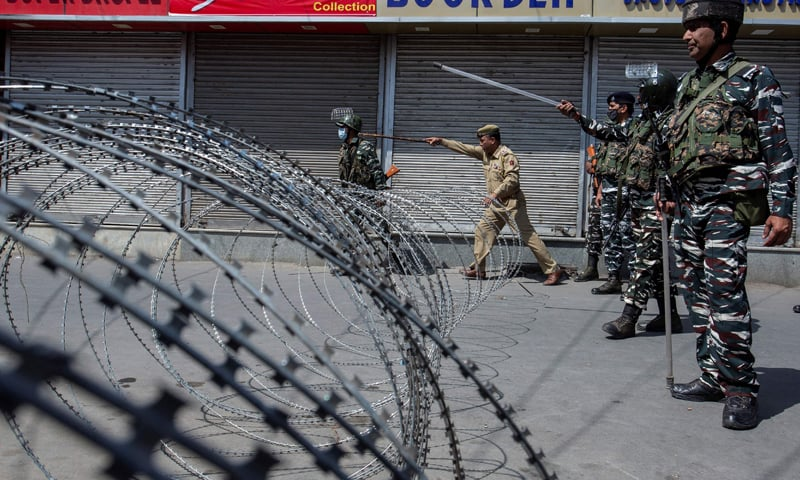 n this file photo, taken on August 17, 2021, Indian forces stand along a street behind a concertina wire during clashes with Kashmiri Muslims defying restrictions for a Muharram procession in Srinagar. — AFP/File