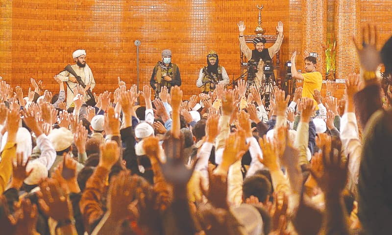 KABUL: Taliban fighters stand next to a prayer leader inside a mosque as the faithful raise their hands before Friday prayers.—AFP