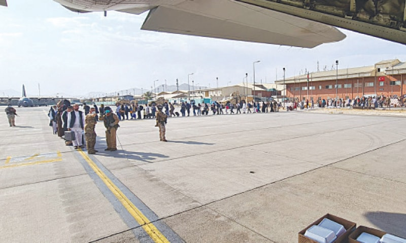 KABUL: Afghans stand in line to be evacuated onto an Italian Airforce plane from Kabul airport on Sunday.—AP