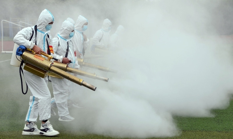 Staff members spray disinfectant at a school ahead of the new semester in Bozhou in China's eastern Anhui province on August 23. — AFP