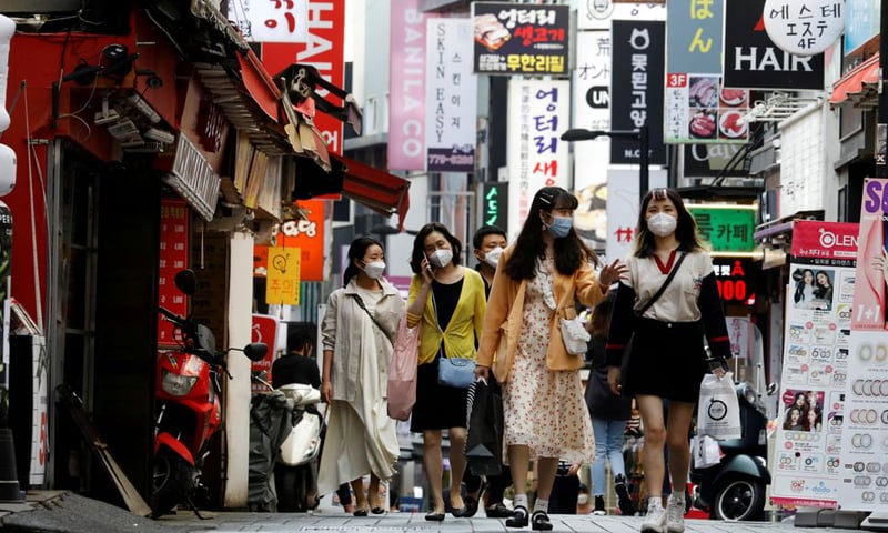 In this file photo, people wearing masks walk at Myeongdong shopping district amid social distancing measures to avoid the spread of Covid-19 in Seoul, South Korea. — Reuters/File