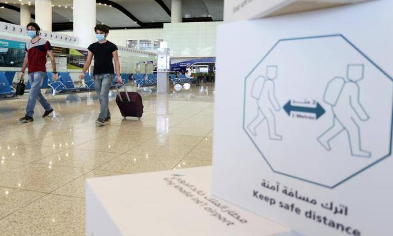 Travellers wearing protective face masks walk at Riyadh International Airport in this file photo. — Reuters