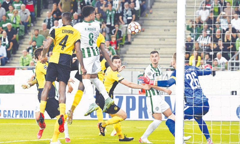 BUDAPEST: Ferencvaros' Ryan Mmaee (top) heads to score during the second leg of their Champions League playoff against BSC Young Boys at the Groupama Arena.—AP