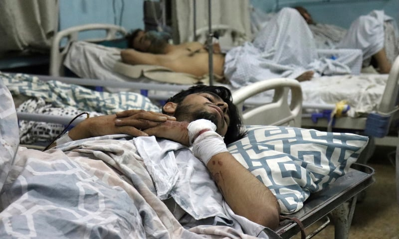Afghans lie on beds at a hospital after they were wounded in the deadly attacks outside the airport in Kabul, Afghanistan on August 26. — AP
