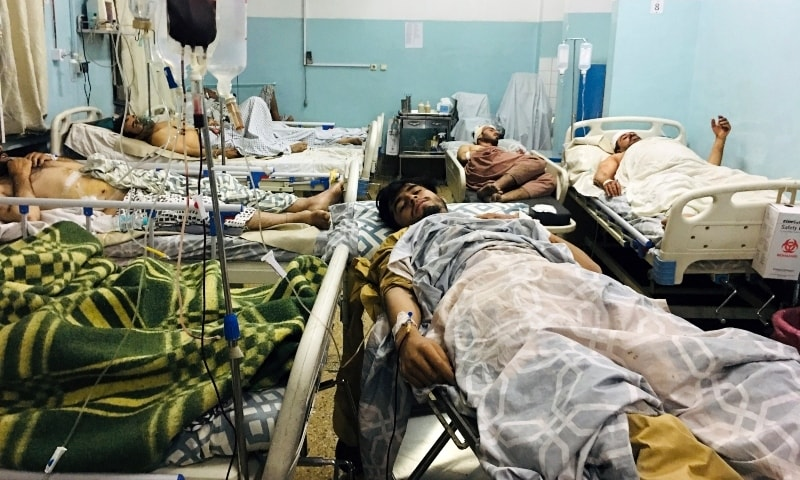 Wounded Afghans lie on a bed at a hospital after a deadly explosion outside the airport in Kabul on August 26. — AP