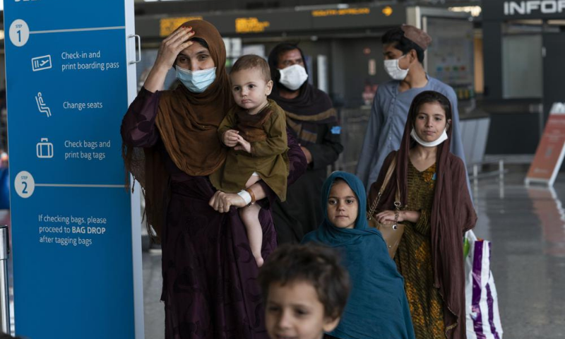 Families evacuated from Kabul, Afghanistan, walk through the terminal before boarding a bus after they arrived at Washington Dulles International Airport, in Chantilly, US, on Friday. — AP