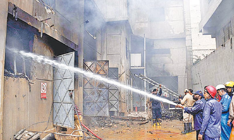 KARACHI: A team of firefighters busy extinguishing the fire at the chemical factory on Friday.—APP