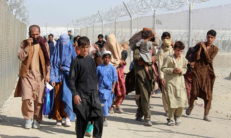 In this file photo, Afghan people walk inside a fenced corridor as they enter Pakistan at the Pakistan-Afghanistan border-crossing point in Chaman on August 25, following the Taliban's stunning military takeover of Afghanistan. — AFP/File