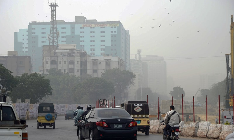 This file photo shows vehicles travelling on a road in Saddar, Karachi in hazy weather. — AFP/File