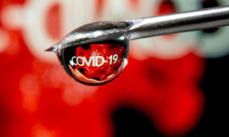 """The word """"COVID-19"""" is reflected in a drop on a syringe needle in this illustration taken November 9, 2020. — Reuters/File"""