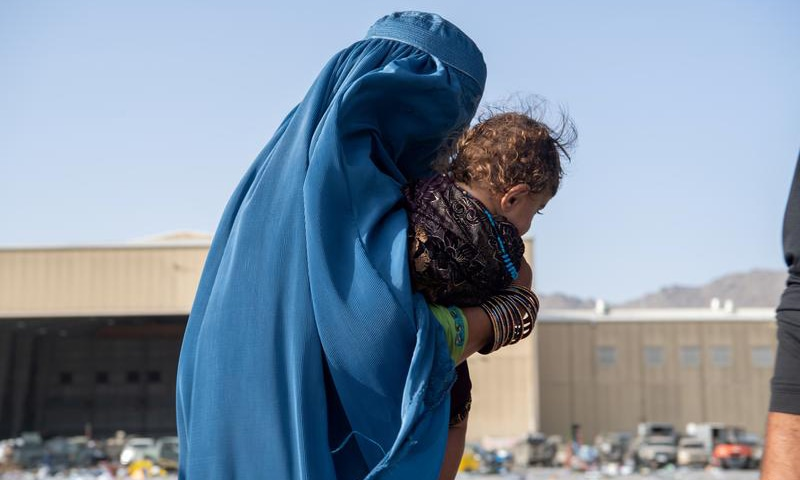 This file photo shows a woman carrying a child as passengers board a US Air Force C-17 Globemaster III assigned to the 816th Expeditionary Airlift Squadron in support of the Afghanistan evacuation at Hamid Karzai International Airport in Kabul, Afghanistan. — Reuters/File