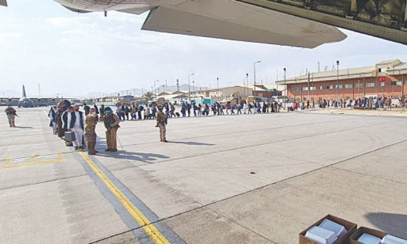 This file photo shows Afghans standing in a line to board a flight at Kabul airport. — AP/File