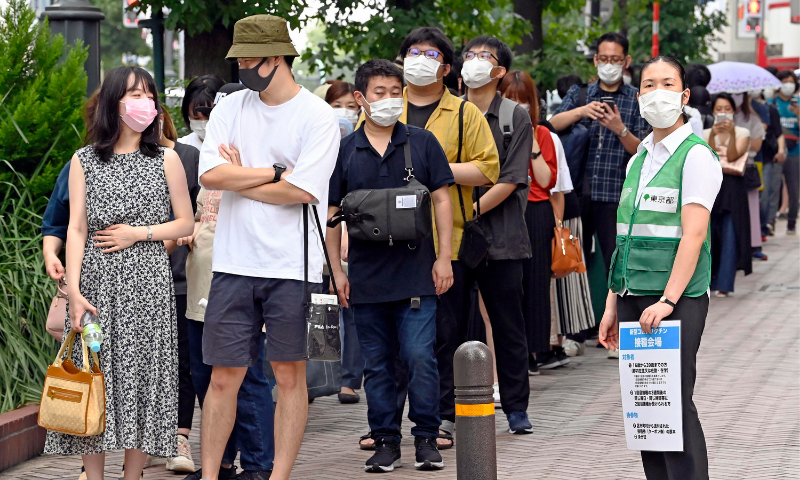 People wait in line to get tickets for the coronavirus vaccine at the Shibuya district in Tokyo on Saturday. — AP