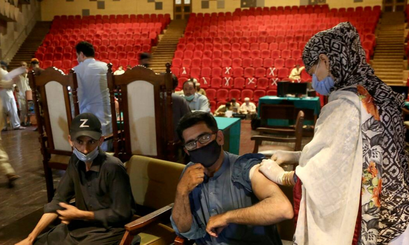 A government employee receives the Covid-19 vaccine from a health worker while others wait their turn at a vaccination centre in Nishtar hall, Peshawar. — AP/File
