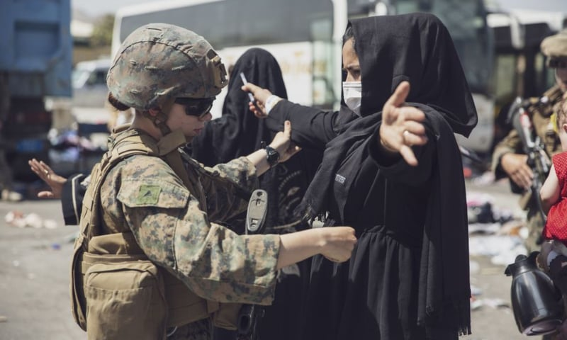 A US Marine checks a woman as she goes through the Evacuation Control Centre during an evacuation at Hamid Karzai International Airport, Kabul, Afghanistan on August 28. — Reuters