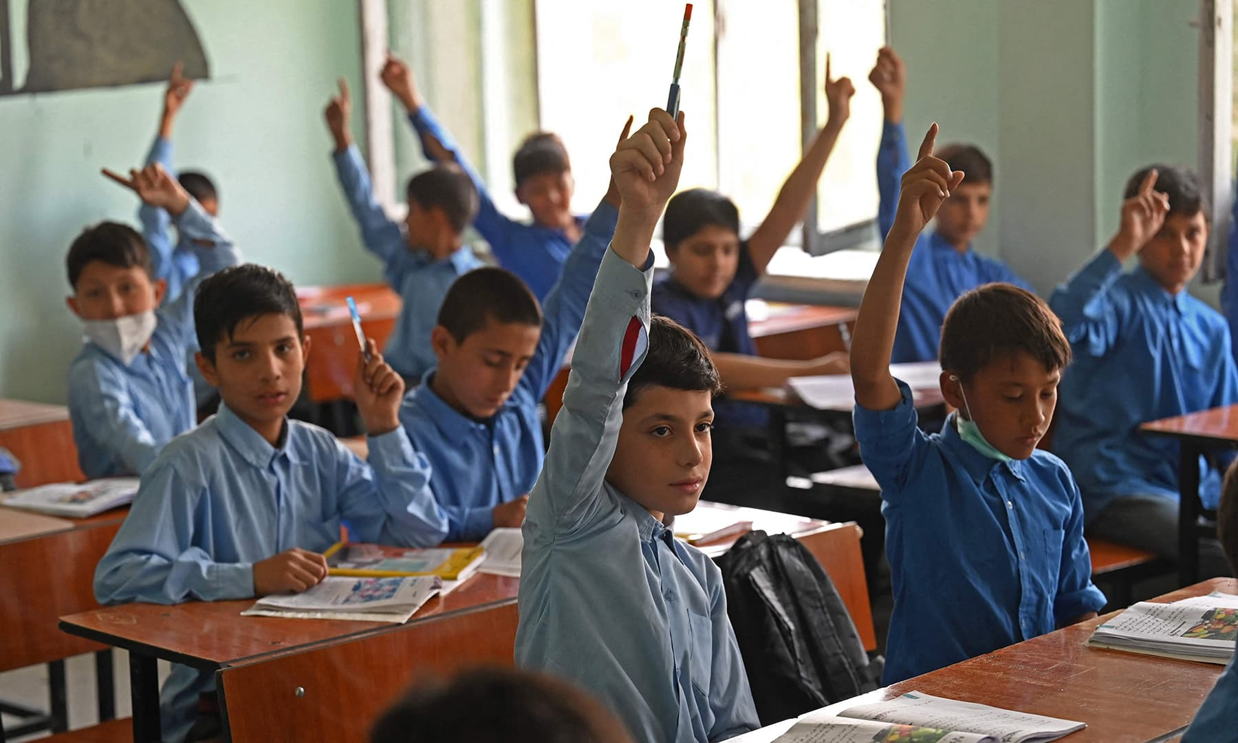 Students attend their class at a government middle school in Kabul on August 30. — AFP