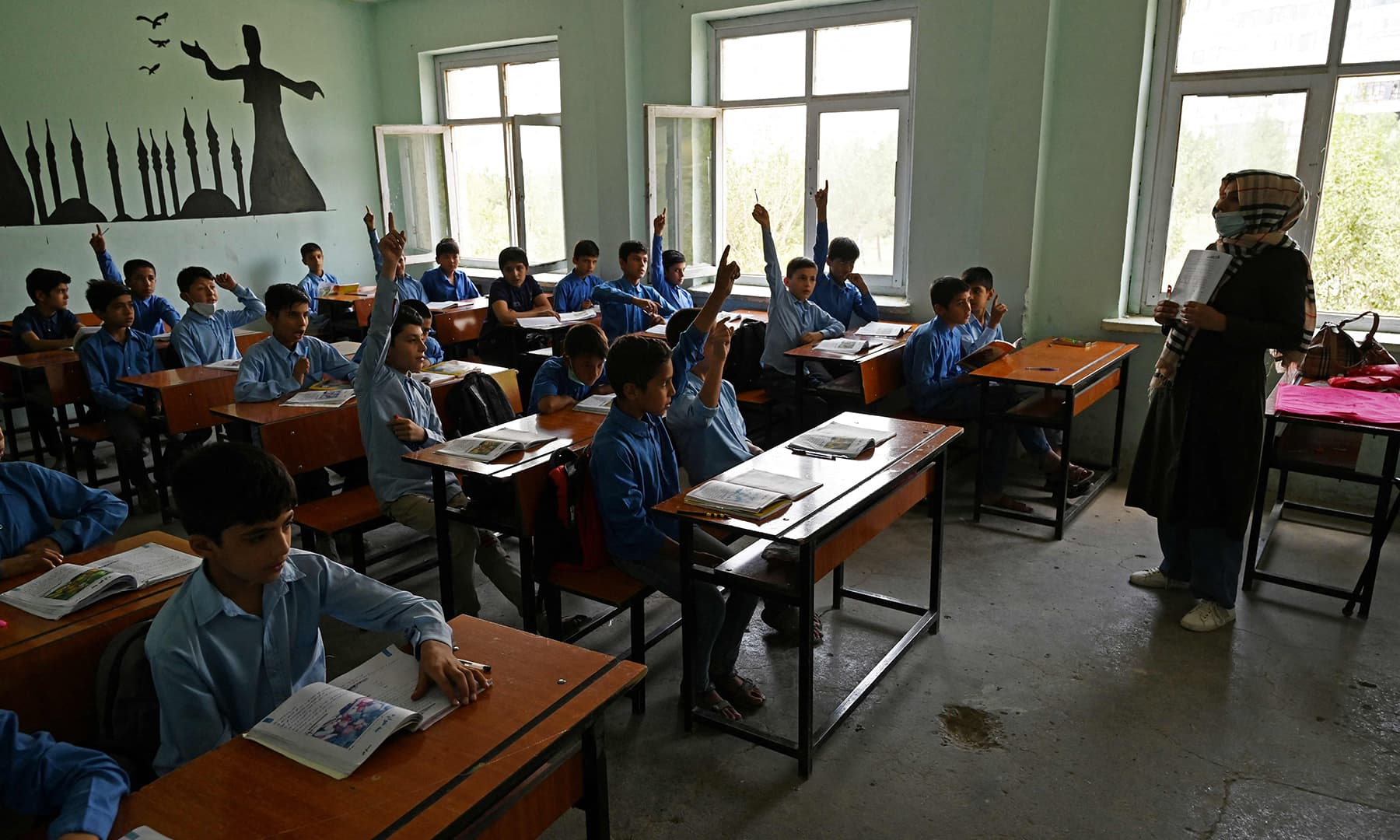A teacher conducts a class at a government middle school in Kabul on August 30. — AFP