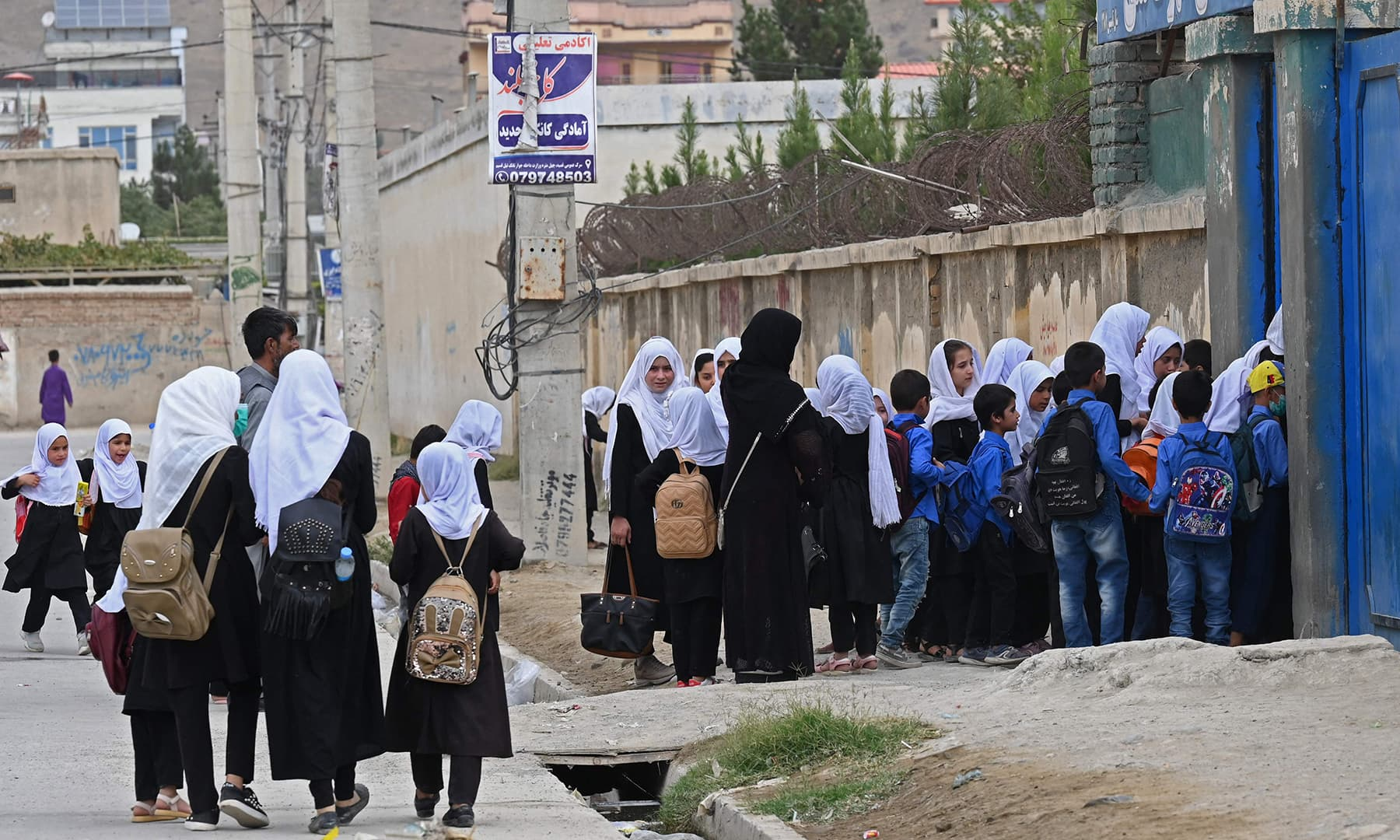 Students arrive to attend their morning classes at a government middle school in Kabul on August 30. — AFP