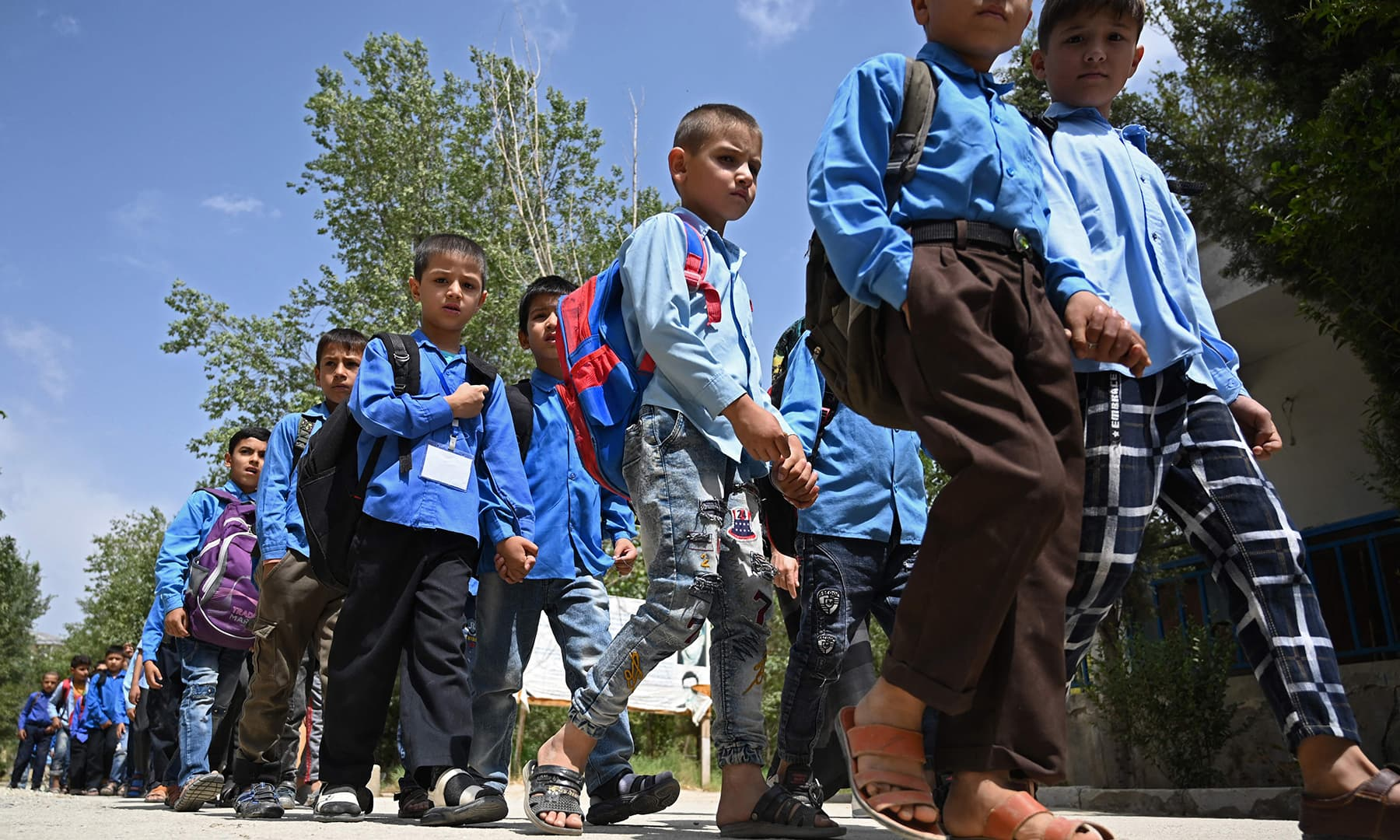 Students walk in a line as they leave after attending their government middle school in Kabul on August 30. — AFP