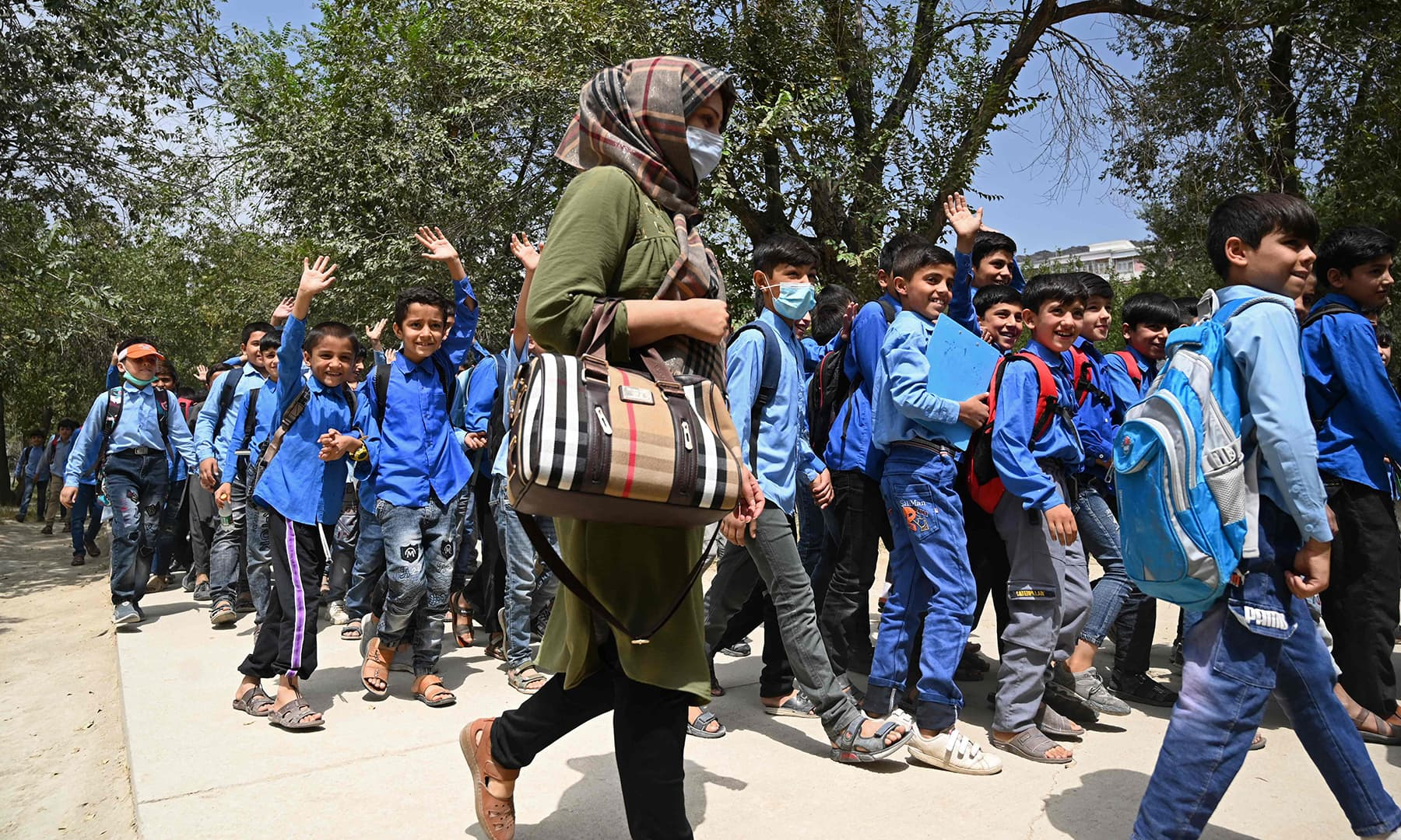 A teacher (C) walks along with students as they leave after attending their government middle school in Kabul on August 30. — AFP