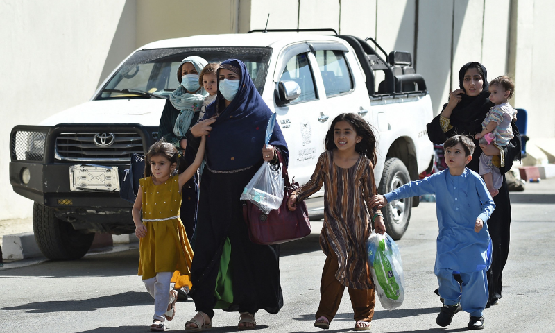 An Afghan woman and children, hoping to leave Afghanistan, walk through the main entrance gate of Kabul airport in Kabul on August 28. — AFP